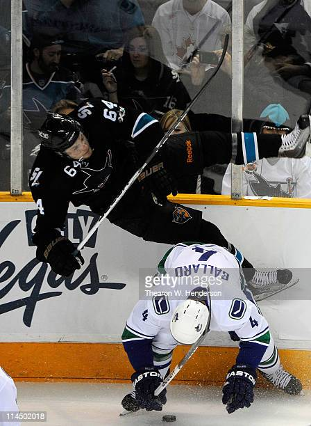 Keith Ballard of the Vancouver Canucks throws the hip check on Jamie McGinn of the San Jose Sharks in the second period in Game Four of the Western...