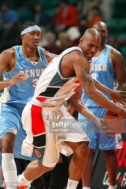 Keith Bogans of the Charlotte Bobcats plays keep away with DeMarr Johnson of the Denver Nuggets on February 16, 2005 at the Charlotte Coliseum in...
