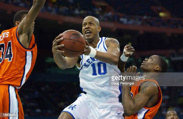 Keith Bogans of the University of Kentucky Wildcats drive the lane between Kyle Davis and Marquis Daniels of the Auburn University Tigers as the...