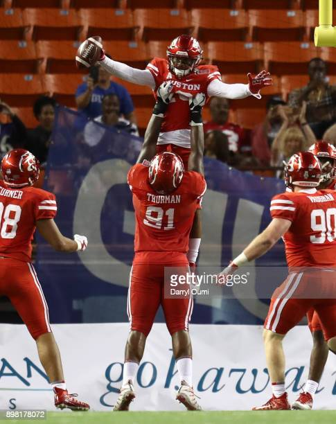 Keith Corbin of the Houston Cougars is held up by teammate Nick Thurman after running back a blocked field goal to score a touchdown during the third...