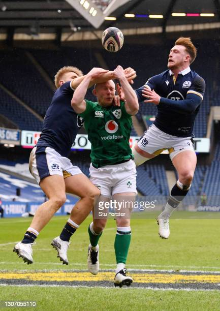 Keith Earls of Ireland competes for the ball with Chris Harris and Stuart Hogg of Scotland leading to the first try scored by Robbie Henshaw during...