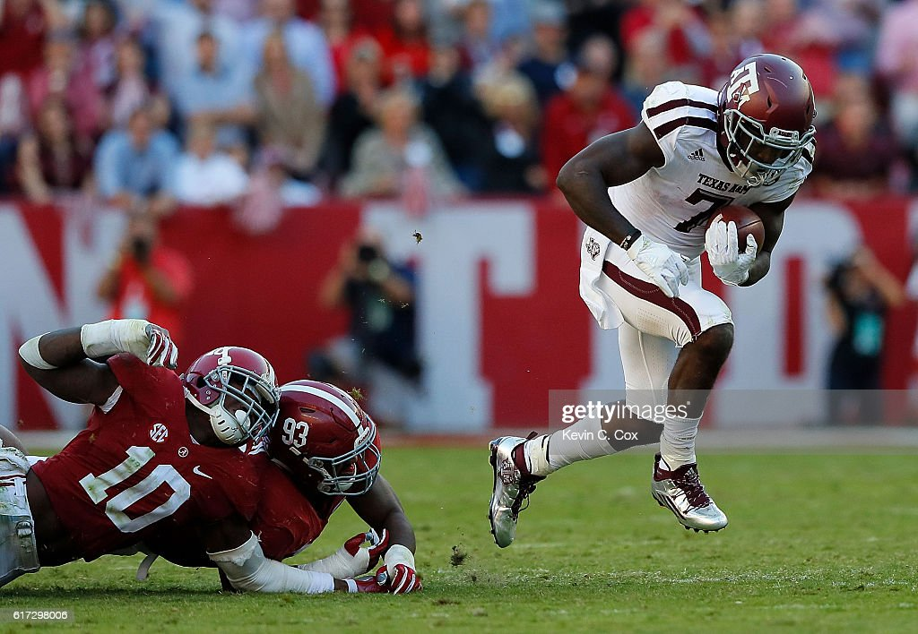 Keith Ford #7 of the Texas A&M Aggies breaks a tackle by Reuben Foster #10 and Jonathan Allen #93 of the Alabama Crimson Tide at Bryant-Denny Stadium on October 22, 2016 in Tuscaloosa, Alabama.