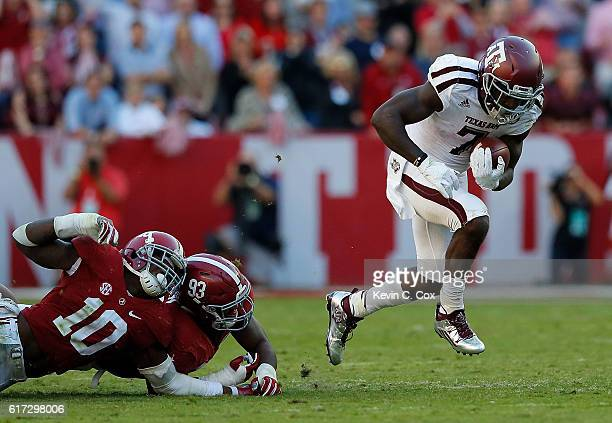 Keith Ford of the Texas AM Aggies breaks a tackle by Reuben Foster and Jonathan Allen of the Alabama Crimson Tide at BryantDenny Stadium on October...