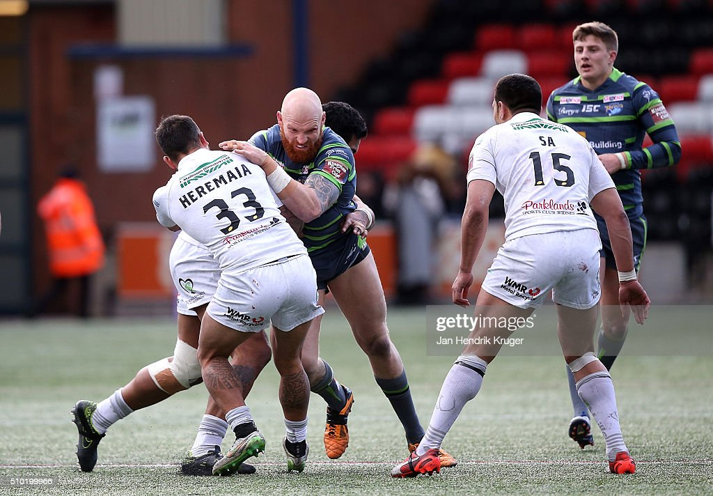 Keith Galloway of Leeds Rhinos is tackled by Aaron Heremaia of Widnes Vikings during the First Utility Super League match between Widnes Vikings and Leeds Rhinos at Select Security Stadium on February 14, 2016 in Widnes, England.
