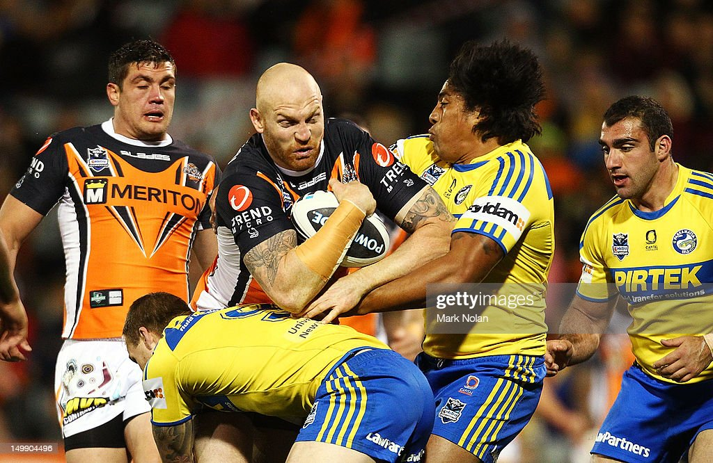 Keith Galloway of the Tigers is tackled during the round 22 NRL match between the Wests Tigers and the Parramatta Eels at Campbelltown Sports Stadium on August 6, 2012 in Sydney, Australia.