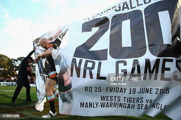 Keith Galloway runs out through a banner for his 200th NRL game during the round 16 NRL match between the Wests Tigers and the Penrith Panthers at...