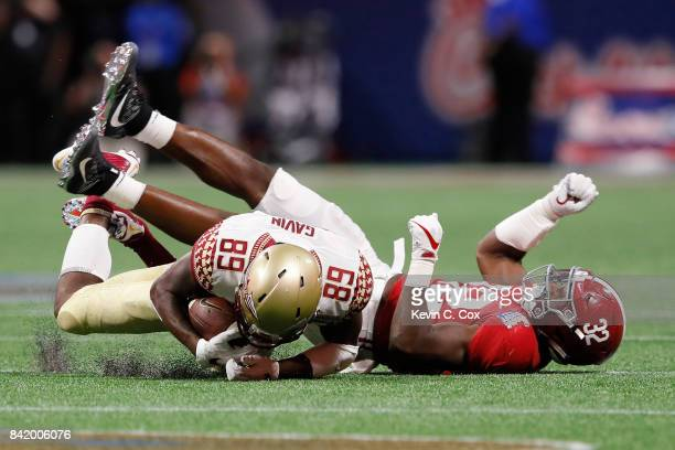Keith Gavin of the Florida State Seminoles is tackled by Rashaan Evans of the Alabama Crimson Tide during their game at MercedesBenz Stadium on...