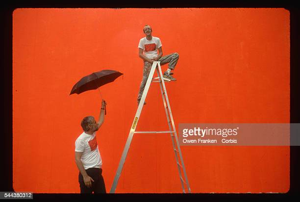 Keith Haring sits on a ladder in front of the bright orange undercoat on which he will shortly paint his mural Crack is Wack New York Park...