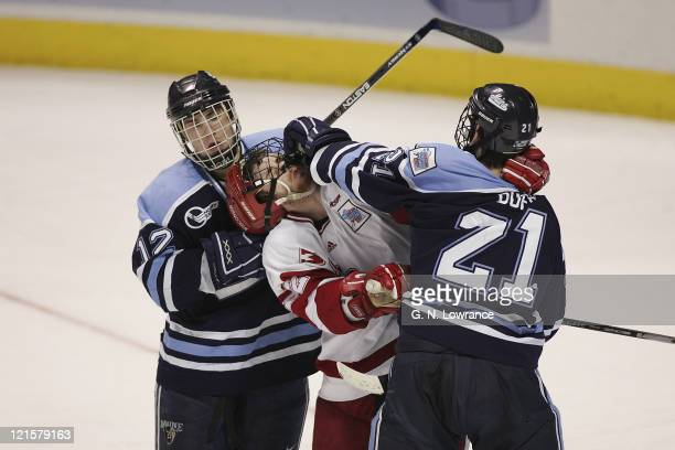 Keith Johnson and Matt Duffy of Maine rough up Wisconsin's Ben Street during 3rd-period action in the semi-finals of the NCAA frozen four at the...
