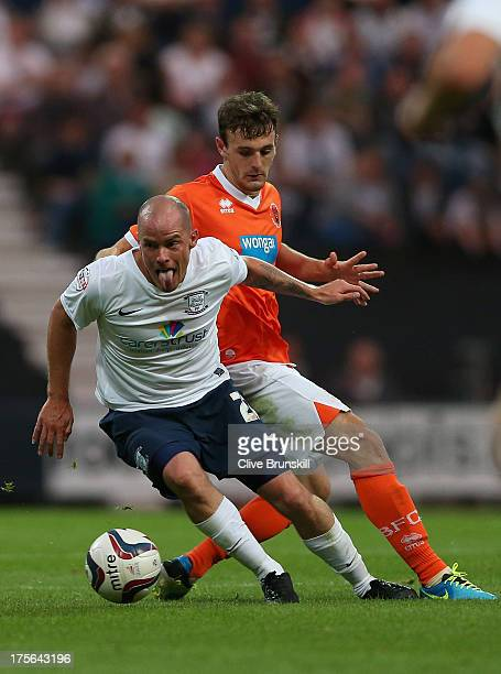 Keith Keane of Preston North End holds off a challenge from Jack Robinson of Blackpool during the Capital One Cup first round match between Preston...