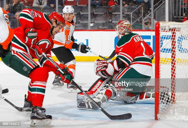 Keith Kinkaid and John Moore of the New Jersey Devils in action against the Philadelphia Flyers on March 16 2017 at Prudential Center in Newark New...