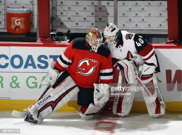 Keith Kinkaid of the New Jersey Devils and Scott Wedgewood of the Arizona Coyotes chat before the game at the Prudential Center on October 28 2017 in...