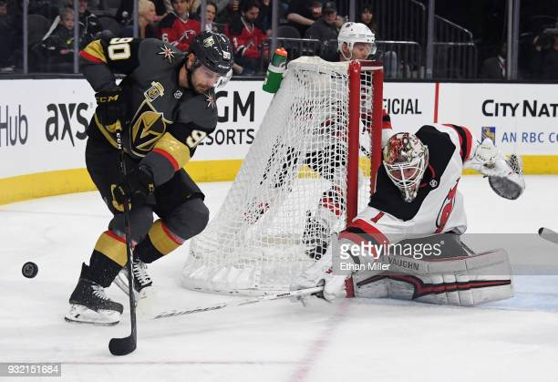 Keith Kinkaid of the New Jersey Devils knocks the puck away from Tomas Tatar of the Vegas Golden Knights in the second period of their game at...