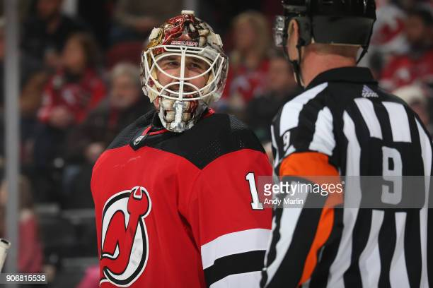Keith Kinkaid of the New Jersey Devils looks on with Referee Dan O'Rourke during the game against the Washington Capitals at Prudential Center on...