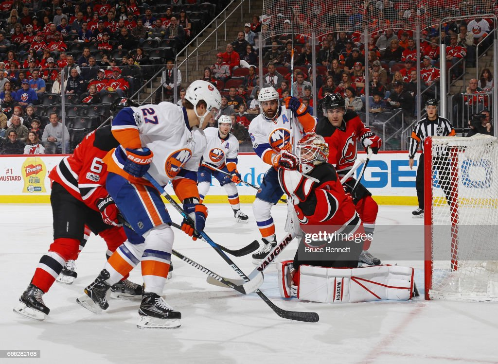 Keith Kinkaid #1 of the New Jersey Devils makes the first period glove save on Anders Lee #27 of the New York Islanders at the Prudential Center on April 8, 2017 in Newark, New Jersey.