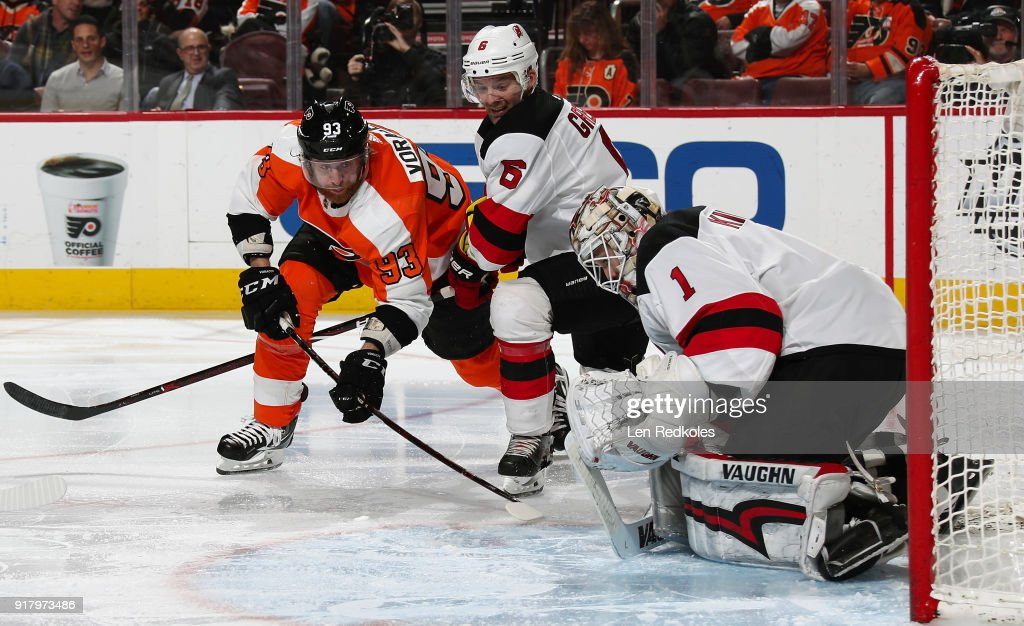 Keith Kinkaid #1 of the New Jersey Devils protects the puck in his pads as Andy Greene #6 defends against Jakub Voracek #93 of the Philadelphia Flyers on February 13, 2018 at the Wells Fargo Center in Philadelphia, Pennsylvania.