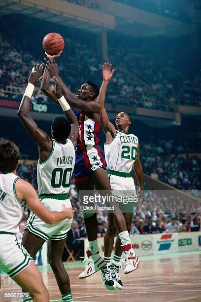Keith Lee of the New Jersey Nets goes up for a shot against Robert Parish and Brian Shaw of the Boston Celtics during a game played in 1989 at the...