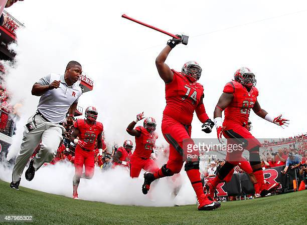 Keith Lumpkin and Eric Wiafe of the Rutgers Scarlet Knights lead their team onto the field for a game against the Washington State Cougars at High...