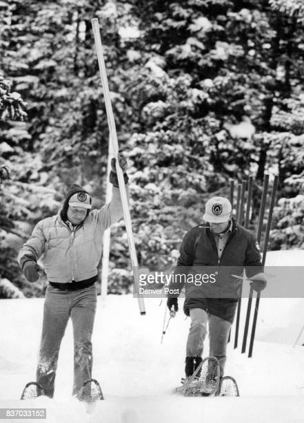 Keith Mackey Rams A Measuring Device Into The Snow to measure its Depth Carroll Hamon stands by on snowshoes to record the data at a testing site...