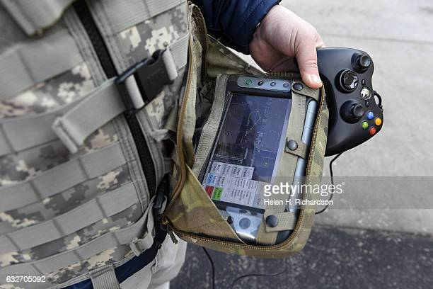 Keith Massie a mechanical engineer at Lockheed Martin shows off a ruggedized tablet computer that used with an Xbox controller helps to drive a Squad...