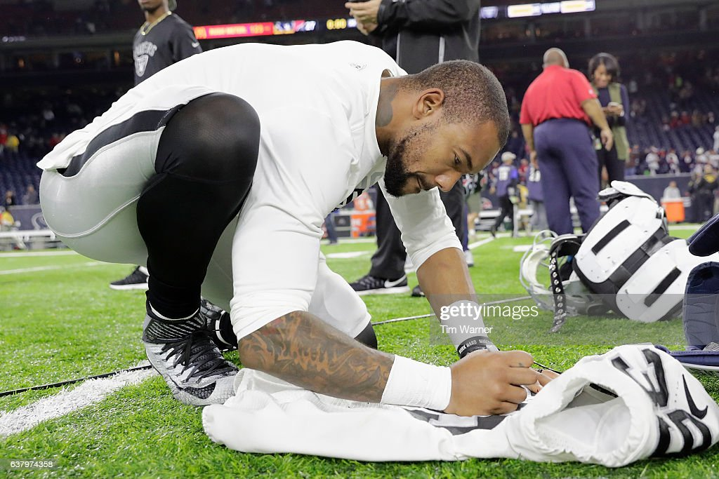 Keith McGill of the Oakland Raiders autographs his jersey after ...