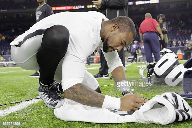 Keith McGill of the Oakland Raiders autographs his jersey after the game against the Houston Texans at NRG Stadium on January 7 2017 in Houston Texas