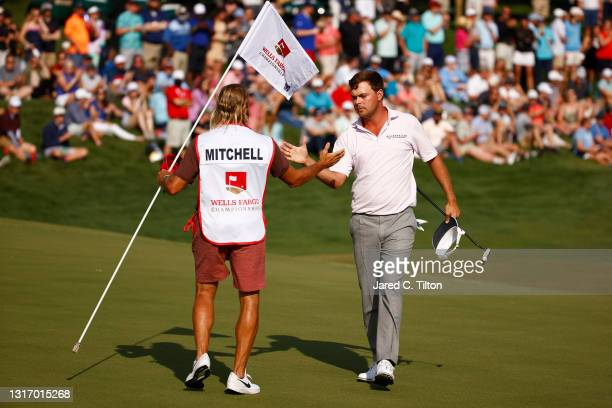 Keith Mitchell of the United States and his caddie Pete Persolja shake hands on the 18th green during the third round of the 2021 Wells Fargo...