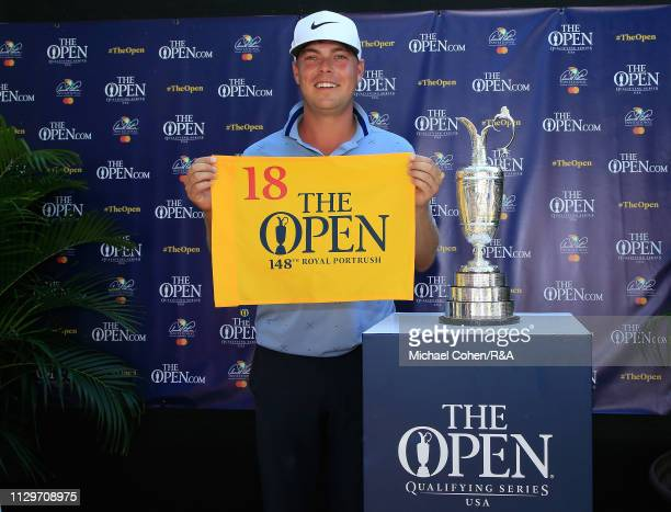 Keith Mitchell of the United States poses with the Claret Jug while holding a hole flag after qualifying for the Open Championship during The Open...