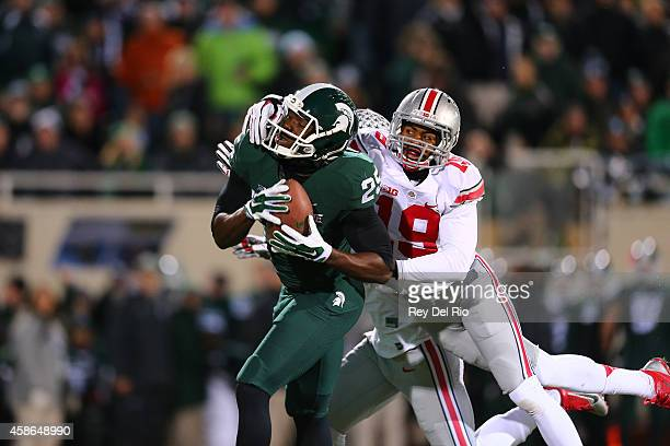 Keith Mumphery of the Michigan State Spartans catches a pass defended by Gareon Conley of the Ohio State Buckeyes at Spartan Stadium on November 8,...