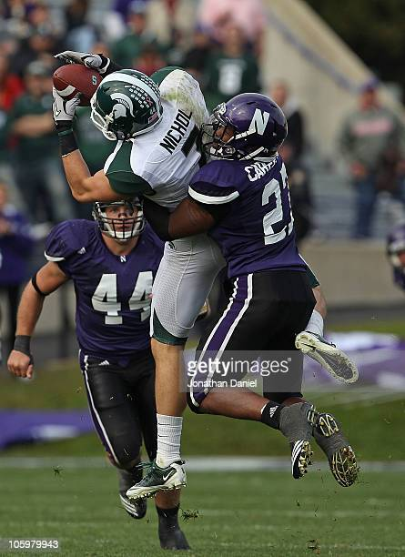 Keith Nichol of the Michigan State Spartans catches a pass as Jared Carpenter of the Northwestern Wildcats makes the hit in the 4th quarter at Ryan...