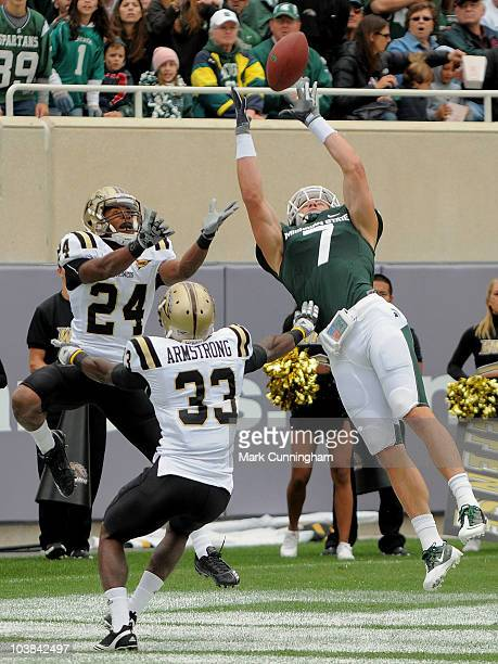 Keith Nichol of the Michigan State Spartans catches a touchdown pass in the second quarter while Mario Armstrong and Lewis Toler of the Western...