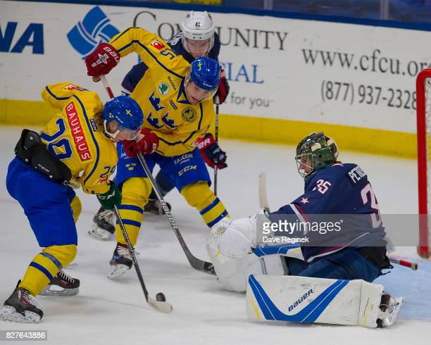 Keith Petruzzelli of the USA makes a save as Lias Andersson and Glenn Gustafsson of Sweden during a World Jr Summer Showcase game at USA Hockey Arena...