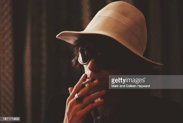 Keith Richards from the Rolling Stones smokes a cigarette while wearing sunglasses and a cream coloured hat circa 1967