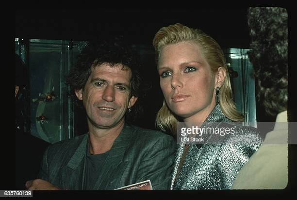 Keith Richards guitarist for the Rolling Stones stands with his wife fashion model Patti Hansen
