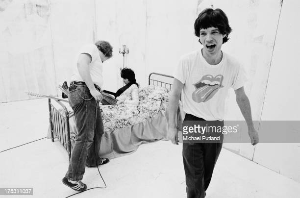 Keith Richards lies on a prop bed as Mick Jagger laughs during the production of the music video for Rolling Stones' 'Respectable' in New York 1978