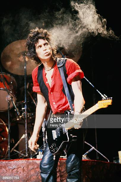 Keith Richards looks up at a cloud of smoke as he performs live with the Rolling Stones