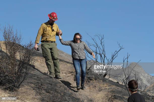 Keith Smyth left from Engine 371 ShastaTrinity NF helps Maria Kirkland walked down a hilltop where she went up to look at her husband and home deep...