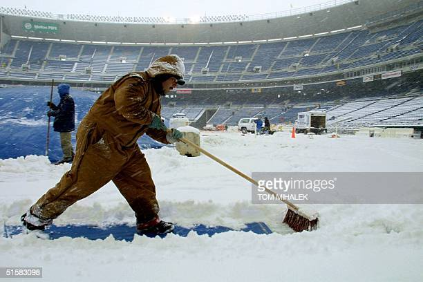 Keith Steigerwald an employee of the city of Philadelphia uses a broom to push snow off of a giant tarp covering the football field inside Veterans...