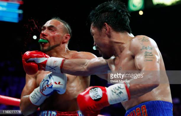 Keith Thurman takes a punch from Manny Pacquiao during their WBA welterweight title fight at the MGM Grand Garden Arena on July 20 2019 in Las Vegas...