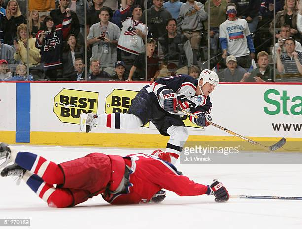 Keith Tkachuk of Team USA shoots the puck into an empty net for his fourth goal past a sprawled Sergei Gonchar of Team Russia in the third period of...