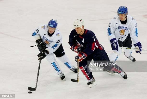 Keith Tkachuk of the United States chases Jussi Kokinen of Finland while Toni Lydman of Finland skates during the quarter final of the men's ice...