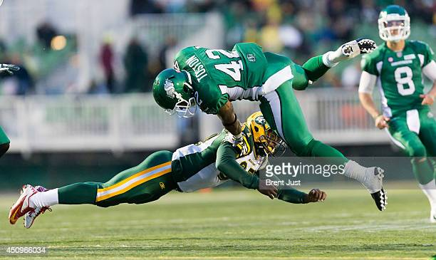 Keith Toston of the Saskatchewan Roughriders is sent into the air by a tackle from Eddie Steele of the Edmonton Eskimos during a preseason game...