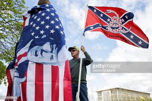 Keith Weber of Centralia Washington holds a flag that combines a Gadsden flag from the American Revolution with a Confederate flag from the American...