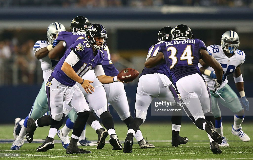 Keith Wenning #10 of the Baltimore Ravens hands off to Lorenzo Taliaferro #34 of the Baltimore Ravens against the Dallas Cowboys in the second half of the preseason game at AT&T Stadium on August 16, 2014 in Arlington, Texas.