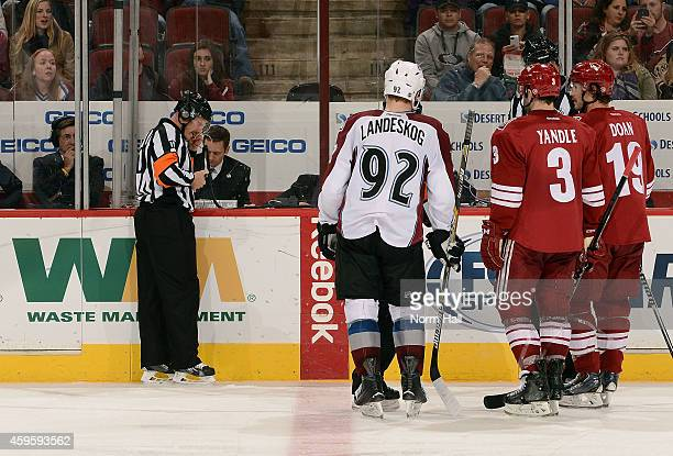 Keith Yandle and Shane Doan of the Arizona Coyotes wait with Gabriel Landeskog the Colorado Avalanche as referee Gord Dwyer reviews an Avalanche goal...