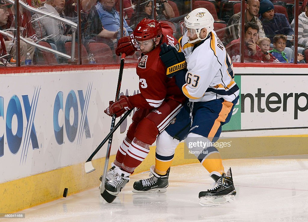 Keith Yandle #3 of the Arizona Coyotes and Mike Ribeiro #63 of the Nashville Predators battle for the puck along the boards during the third period at Gila River Arena on December 11, 2014 in Glendale, Arizona.