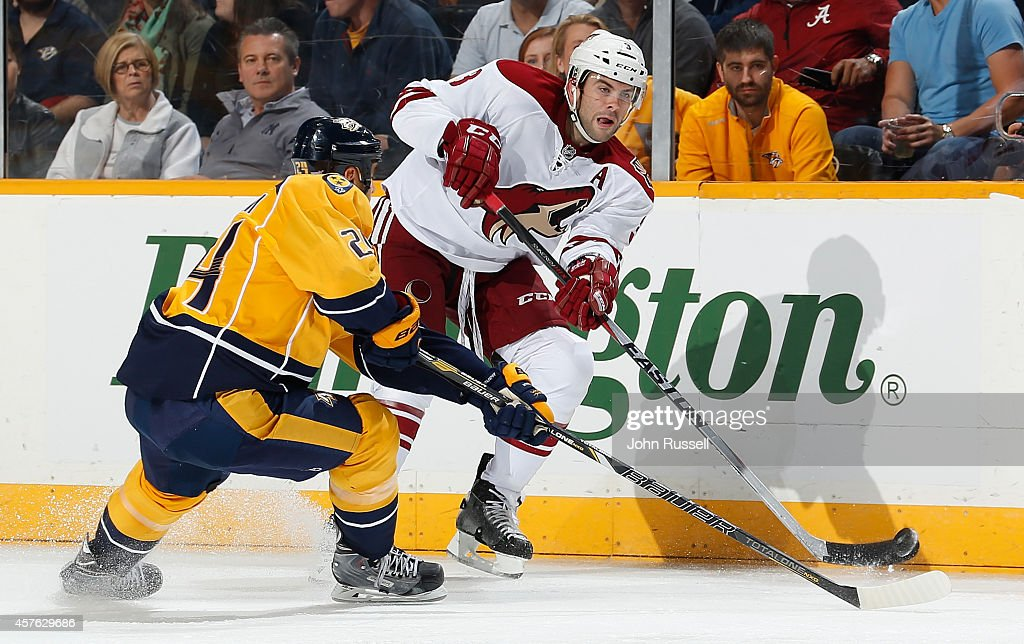 Keith Yandle #3 of the Arizona Coyotes skates the puck against Eric Nystrom #24 of the Nashville Predators in his 500th NHL game on October 21, 2014 at Bridgestone Arena in Nashville, Tennessee.
