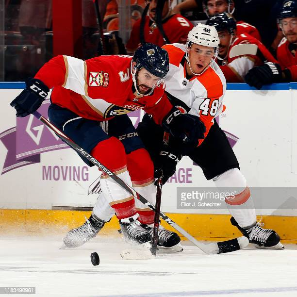 Keith Yandle of the Florida Panthers crosses sticks with Morgan Frost of the Philadelphia Flyers at the BBT Center on November 19 2019 in Sunrise...