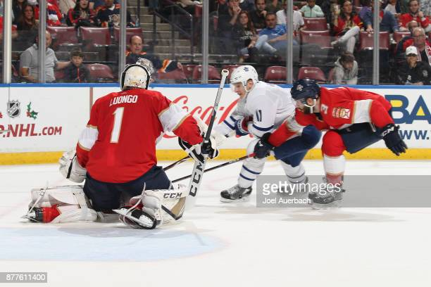 Keith Yandle of the Florida Panthers defends against Zach Hyman of the Toronto Maple Leafs as goaltender Roberto Luongo guards the post during second...