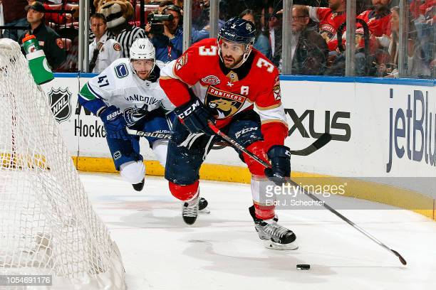 Keith Yandle of the Florida Panthers skates with the puck against Sven Baertschi of the Vancouver Canucks at the BBT Center on October 13 2018 in...